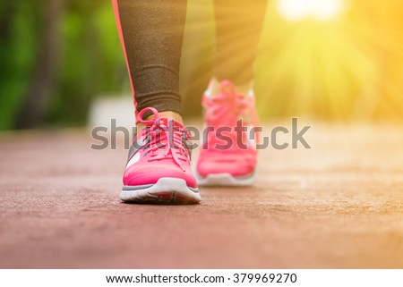 Fitness woman training and jogging in summer park, close up on running shoes in sunlight. Healthy lifestyle and sport concept  - stock photo