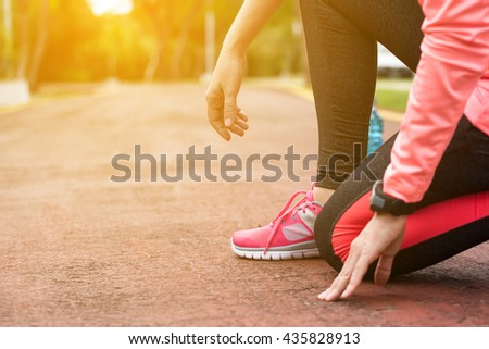 Fitness woman training and jogging in summer park. Sitting  and having a rest. Healthy lifestyle and sport concept