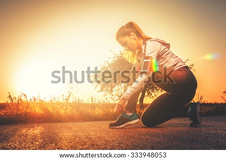Fitness woman tying laces on her sneakers preparing for running outdoors