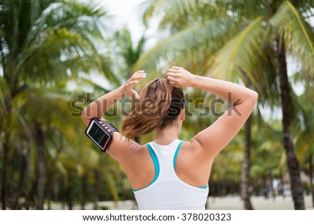 Fitness woman tying ponytail and getting ready for beach outdoor workout. Female athlete on tropical vacation wearing cellphone armband.
