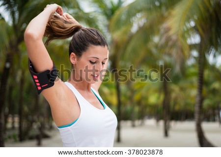 Fitness woman tying ponytail and getting ready for beach outdoor workout. Female athlete preparing for exercising. - stock photo