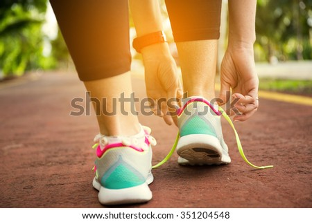 Fitness woman tying running shoe laces, ready for jogging in summer park. Healthy lifestyle and sport concept - stock photo