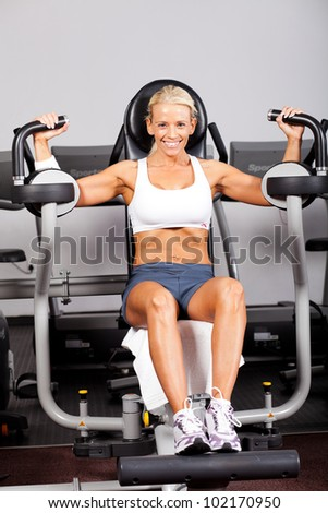 fitness woman using peck deck machine in gym - stock photo