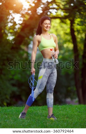 Fitness woman with a skipping rope and a bottle of water outdoors. Fitness training outdoors. Fitness classes outdoors. Attractive fitness woman. Workout outdoors. Healthy lifestyle. - stock photo