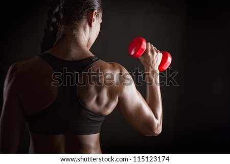 Fitness woman with barbells on dark background - stock photo