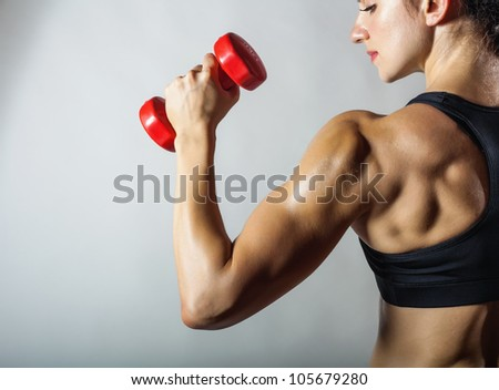 Fitness woman with barbells on grey background - stock photo