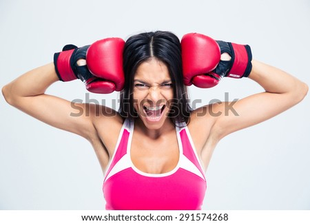 Fitness woman with boxing gloves screaming over gray background - stock photo