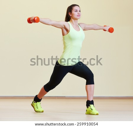 fitness woman with dumbbells at the gym exercising - stock photo