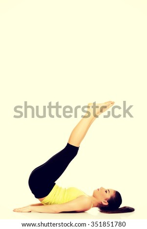 Fitness woman with her legs up practising yoga. - stock photo