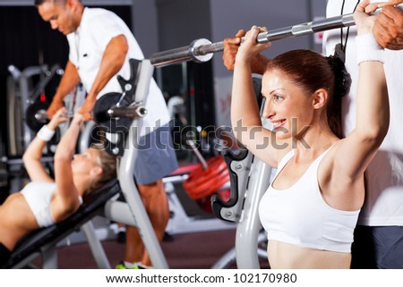 fitness woman with personal trainer in gym - stock photo