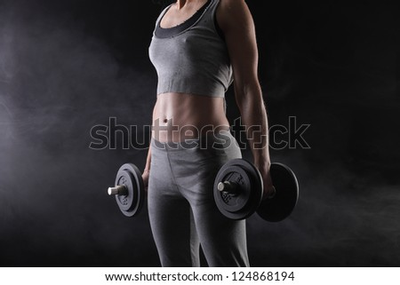 Fitness woman with weights on dark background - stock photo
