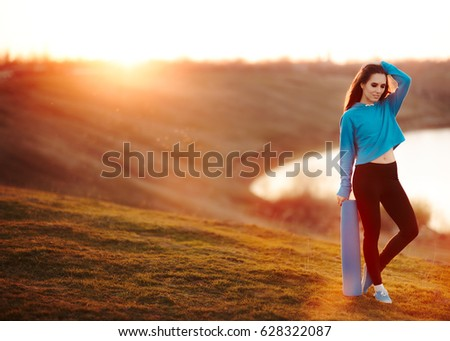 Fitness Woman with Yoga Mat in Nature at Sunset - Beautiful fit girl relaxing in amazing scenery