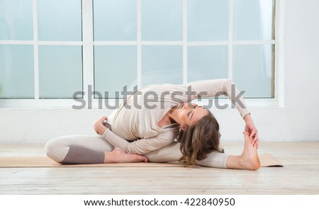 Fitness woman. Woman in the window background. Space for text. Yoga class. Woman doing yoga exercises on mat in gym.