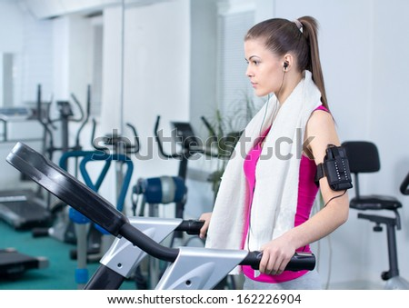 Fitness Woman. Woman runs on a treadmill, exercise in the sport club - stock photo