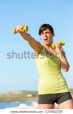 Fitness woman working out on beach in summer. Sporty girl punching and boxing with dumbbells. Hard exercising and training.