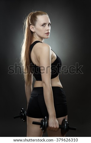 fitness woman working out using dumbbells shot in the studio