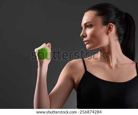 Fitness woman working out with green dumbbell looking at the side on dark background. Fitness concept - stock photo