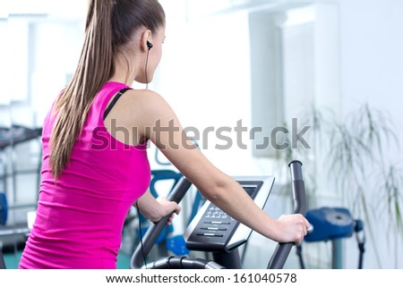 Fitness Woman. Young sporty woman doing exercise on bicycle in the gym centre. - stock photo