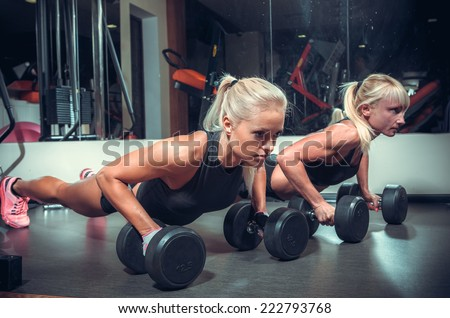 fitness women doing push up in the gym - stock photo