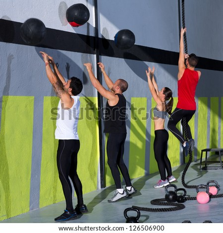 Fitness workout people group with wall balls and rope at fitness gym - stock photo