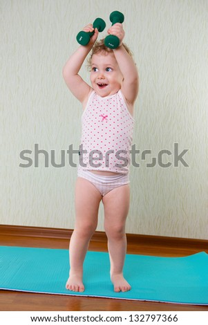 Fitness workout with dumbbells for cute little girl