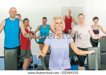 Fitness young group on treadmill running trainer at health gym - stock photo