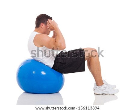 fitness young man doing exercises on gym ball isolated on white - stock photo