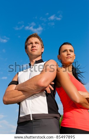 Fitness - Young sportive couple in front of a blue sky on a beautiful summer day outdoors