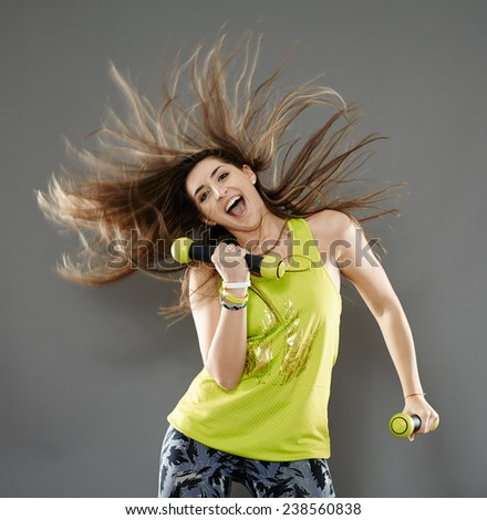 Fitness young woman doing cardio aerobic exercises with light dumbbells - stock photo