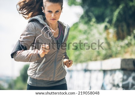 Fitness young woman jogging in the city park - stock photo