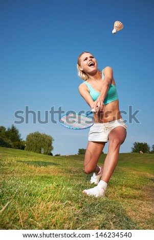 Fitness, young woman playing badminton in a city park - stock photo