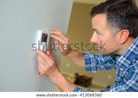 Fitting a thermostat - stock photo