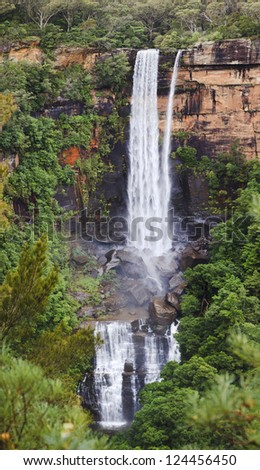 Fitzroy Fall vertical panoramic view at tall water stream blurred in lush green foliage sandstone rock in Blue Mountains Australia