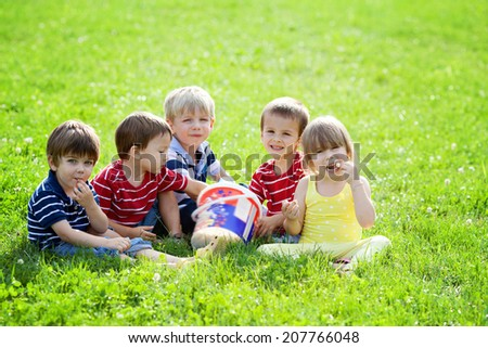 Five adorable kids, eating popcorn in the park - stock photo