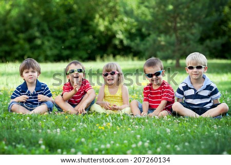 Five adorable kids, lying on the grass, smiling, having fun, wearing glasses