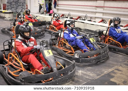 Five adults and one child in helmets prepares for driving karting