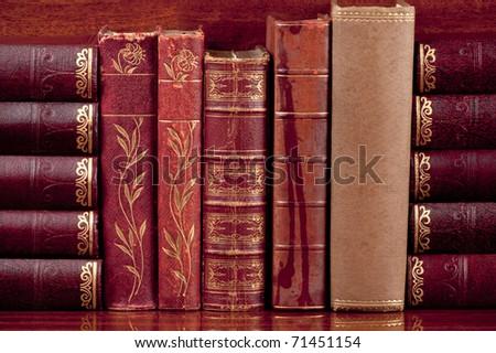 Five antique  books  standing up on a polished wooden shelf supported by other old books on their sides. - stock photo