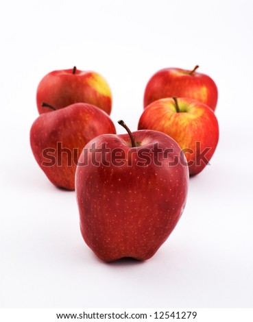 Five apples on white background with shallow depth of field