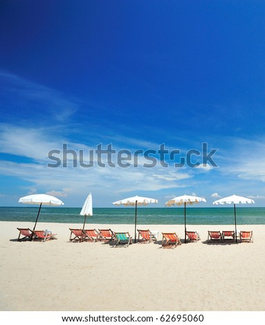 Five Beach chairs with umbrella and clear blue sky