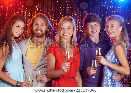 Five beautiful friends holding champagne flutes and smiling at camera