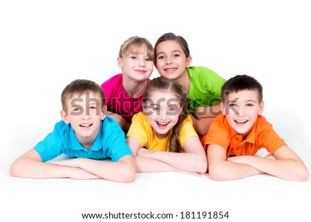 Five beautiful smiling kids lying on the floor in bright colorful t-shirts -  isolated on white. - stock photo