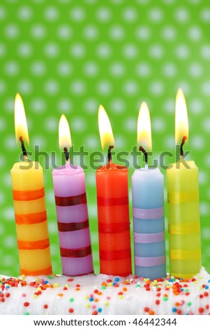 Five birthday candles on green background