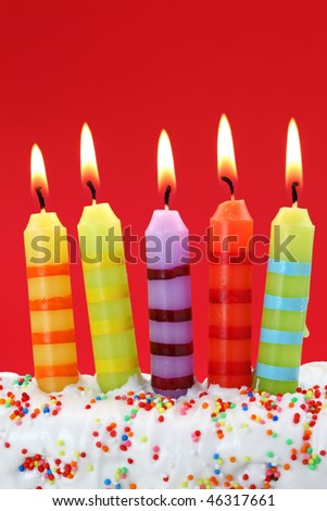 Five birthday candles on red background