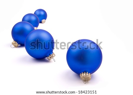 Five blue Christmas Tree ornaments on a field of white. - stock photo