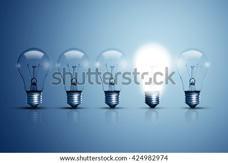 Five bulbs on a blue background and one of them is glowing. - stock photo