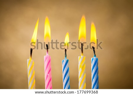 Five burning birthday candles over yellow background