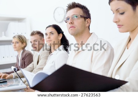 Five business colleagues sitting in a row on a business training and paying attention, looking ahead. Selective focus placed on men in front. - stock photo