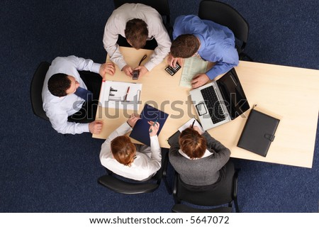 five business people meeting - Businesspeople gathered around a table for a meeting, brainstorming. Aerial shot taken from directly above the table.