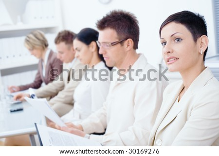Five business people sitting in a row and writing notes on a business training. Selective focus placed on businesswoman in front.