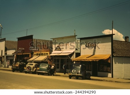 Five businesses on the main street of Cascade Idaho include two bars a cafe drug store and barber shop. 1943 photo by Russell lee. - stock photo